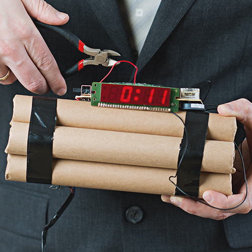 Concept of leadership under difficult circumstances: Businessman disarms a bomb with a wire cutter while it is counting down.